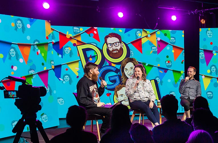 Matt, Jess and Dave from Do Go On Podcast standing on stage at a live show